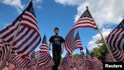 Jackson Tucker šeta kroz polje u parku u mjestu Winnetka u Illinoisu, sa 3.000 američkih zastava postavljenih u znak sećanja na živote izgubljene u napadima 11. septembra 2001.