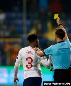 Sudija Aleksej Kulbakov dodeljuje žuti karton engleskom fudbaleru Deniju Rouzu
