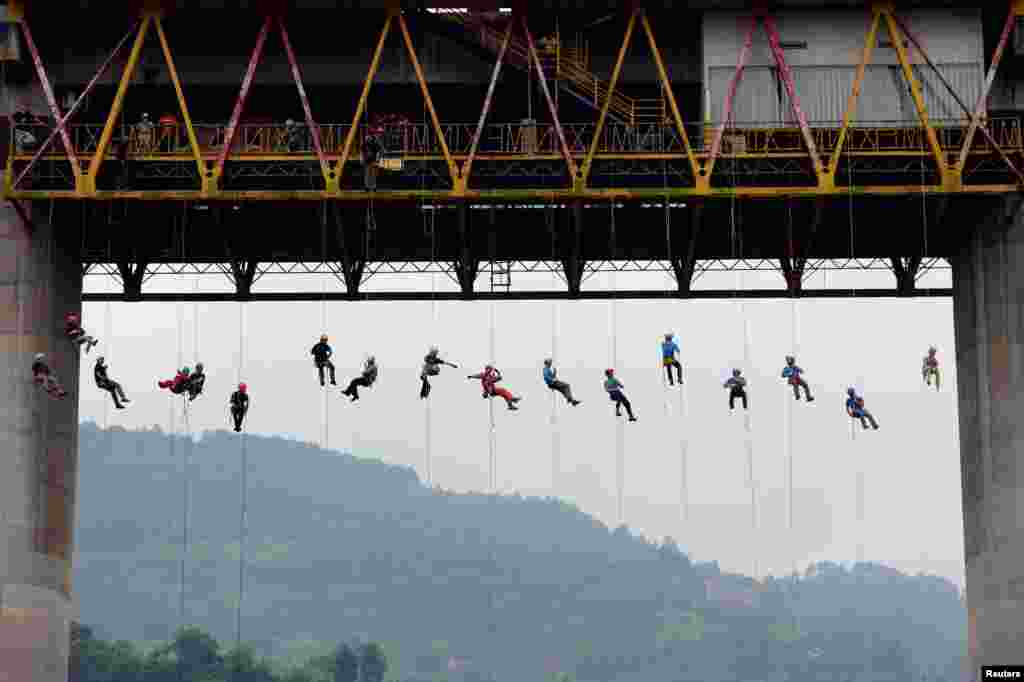 People slide down a rope from a bridge during a rescue training in Chongqing, China, May 22, 2016.