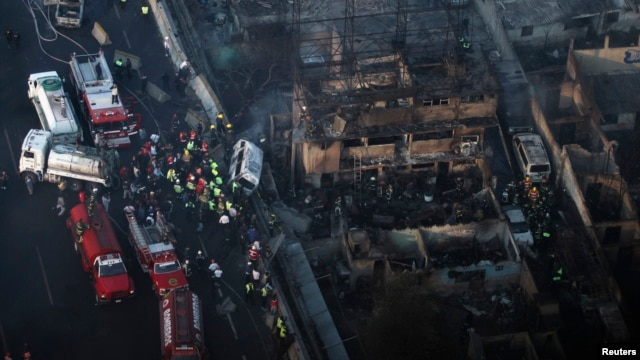 Firefighters and rescue workers stand amidst the rubble of destroyed houses after the explosion of a gas tanker truck in Ecatepec, on the outskirts of Mexico City, May 7, 2013.