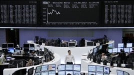Traders at their desks in front of the DAX board at the Frankfurt stock exchange, August 14, 2012.