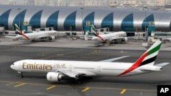 FILE - An Emirates plane taxis to a gate at Dubai International Airport at Dubai International Airport in Dubai, United Arab Emirates.