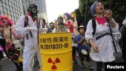 Para demonstran anti PLTN mengenakan masker melakukan unjuk rasa di depan kantor pusat perusahaan listrik Jepang, TEPCO, di Tokyo Minggu (29/7). Demonstran menentang doperasikannya kembali dua PLTN di Jepang.
