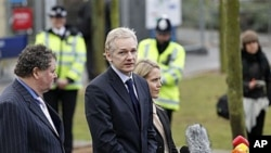 WikiLeaks founder Julian Assange, center, speaks to the media flanked by his lawyers Mark Stephens, left, and Jennifer Robinson, after making an appearance at Belmarsh Magistrates' Court in London, Jan 11, 2011