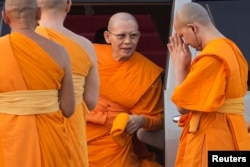 FILE - Phra Dhammachayo, center, arrives for a ceremony at the Dhammakaya Temple in Pathum Thani province, north of Bangkok, on Makha Bucha Day, March 4, 2015.