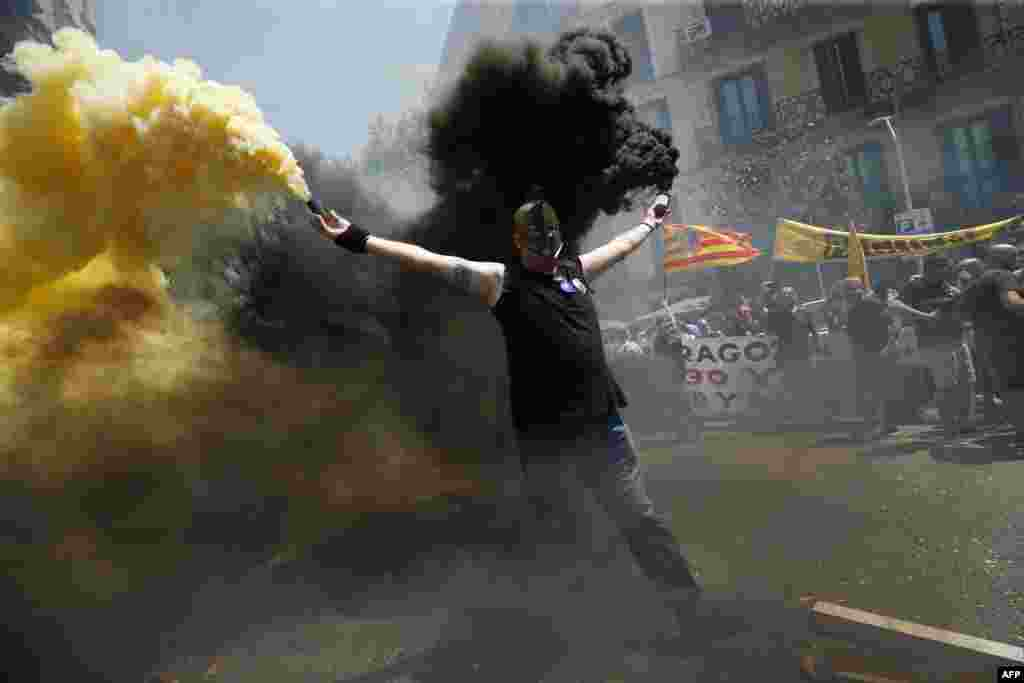 A taxi driver holds flares as protesters gather outside the government delegation office during a strike by cab drivers in Barcelona.