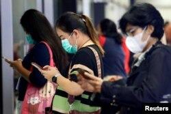 Para penumpang perempuan mengenakan masker menunggu MRT, di Jakarta, 4 Maret 2020. (Foto: Reuters)