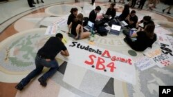 FILE - Students gather in the Texas Capitol to oppose SB4, an anti-sanctuary-cities bill that seeks to jail sheriffs and other officials who refuse to help enforce federal immigration law, in Austin, Texas, April 26, 2017. The legislature passed the bill May 3, 2017.