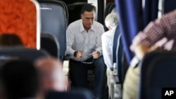 Republican presidential candidate and former Massachusetts Governor Mitt Romney talks with Senator Rob Portman who has also been his debate practice partner, on his campaign charter plane en route to Denver, Colorado, October 1, 2012.