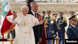 Pope Benedict XVI waves upon his arrival at Beirut international airport as he is welcomed by Lebanon's President Michel Suleiman, September 14, 2012.