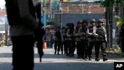 Petugas kepolisian berjalan melewati Markas Korps Brimob menyusul kerusuhan di rutan Mako Brimob Kelapa Dua, Depok, Rabu, 9 Mei 2018.