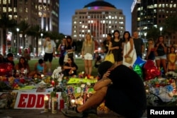 FILE - Mourners gather at a makeshift memorial in downtown Orlando for victims of the gay nightclub shooting, in Orlando, Florida, June 14, 2016.