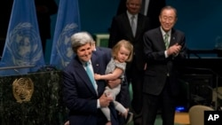 United Nations Secretary-General Ban Ki-moon, left, claps after U.S. Secretary of State John Kerry signs the Paris Agreement on climate change with his granddaughter Isabelle Dobbs Higginson, Friday, April 22, 2016 at U.N. headquarters. (AP Photo/Mary Altaffer)