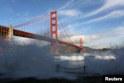 FILE - Waves crash against a sea wall in San Francisco Bay beneath the Golden Gate Bridge in San Francisco, California, Dec. 16, 2014.