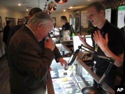 El senador estatal republicano de Nevada Don Gustavson, huele una muestra de marihuana en un dispensario médico durante una breve visita al establecimiento, el viernes 24 de marzo de 2017.