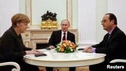 La canciller alemana, Angela Merkell, junto al presidente ruso, Vladimir Putin, y el mandatario francés, François Hollande.