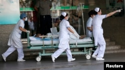 Medical personnel transport a victim of a factory explosion at a hospital in Kunshan, Jiangsu province, August 2, 2014.
