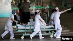 Nhân viên y tế đưa nạn nhân vụ nổ nhà máy phụ tùng xe hơi gần Thượng Hải, ngày 2/8/2014.