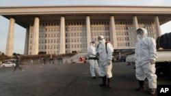 穿著防護裝束的人員在韓國國會大廈外進行消毒(資料照片)