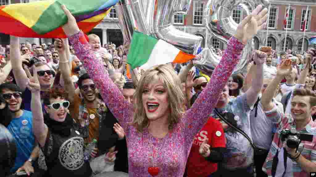 Warga merayakan hasil referendum yang menyetujui pernikahan sesama jenis di Kastil Dublin, Irlandia (23/5). (AP/Peter Morrison)