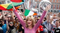 "FILE- Rory O'Neill, known by the Drag persona Panti, celebrates the referendum result with ""yes"" supporters at Dublin Castle, Ireland, May 23, 2015."