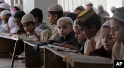 FILE - Pakistani children attend lessons at a madrassa, or a religious school, to learn Quran, in Karachi, Pakistan, Sept. 2, 2015.