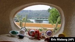 "In this photo taken Monday, April 1, 2019, a window in a sunken room called ""The Happy Place,"" looks out on Interstate 280 from inside the Flintstone House in Hillsborough, Calif."