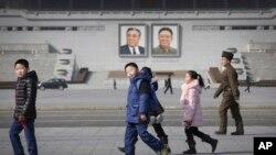 지난 13일 김일성, 김정일 초상화가 걸려있는 평양 광장에서 북한 주민들이 오가고 있다.