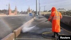 在俄羅斯莫斯科市中心克里姆林宮附近,一名工作人員正在進行消毒,以防止新冠病毒傳播。(2020年4月24日)