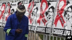 A man uses his mobile phone while passing World AIDS Day banners in Sandton, Johannesburg, South Africa, Dec. 1, 2014.