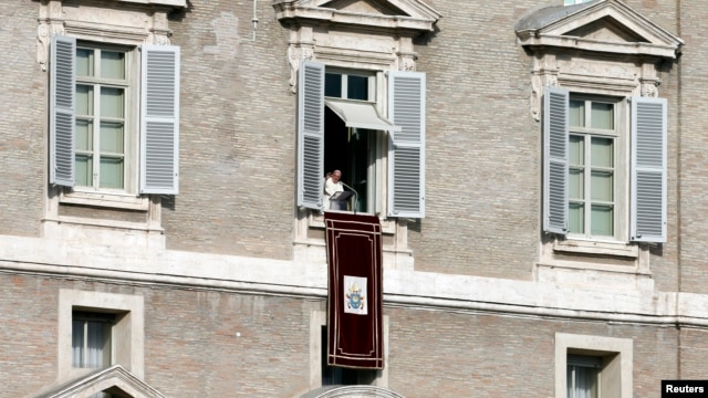 Pope Francis is seen in the window of the Apostolic Palace in Saint Peter's Square at the Vatican, Jan. 1, 2014.