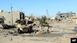 지난 14일 이라크 바그다드 서부 라마디에서 이라크 정부군이 파괴된 장갑차 주변을 수색하고 있다. (자료사진)