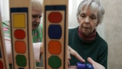 A patient with dementia, right, works on a puzzle with caregivers at the Morning Glory Retirement Home in State Line, Pennsylvania