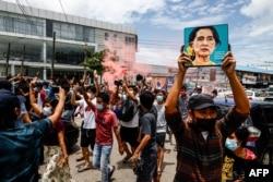 រូបឯកសារ៖ បាតុករភូមាម្នាក់លើករូបថតអ្នកស្រី Aung San Suu Kyi មេដឹកនាំរដ្ឋាភិបាលស៊ីវិលភូមាដែលត្រូវបានដកចេញពីតំណែង ក្នុងអំឡុងនៃបាតុកម្មមួយប្រឆាំងនឹងរបបយោធាកាលពីថ្ងៃទី១៩ ខែមិថុនា ឆ្នាំ២០២១។