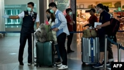 Chinese tourists wearing facemasks arrive Ngurah Rai airport in Denpasar on February 8, 2020. - The new coronavirus that emerged in a Chinese market at the end of last year has killed more than 700 people and spread around the world. (Photo by SONNY TUMBELAKA / AFP)