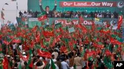 Para pendukung partai Pakistan Tehreek-e-Insaf dipimpin politisi dan bintang olah raga cricket, Imran Khan, meneriakkan slogan sambil melambaikan bendera partainya menentang serangan drone di Peshawar, Pakistan (23/11).
