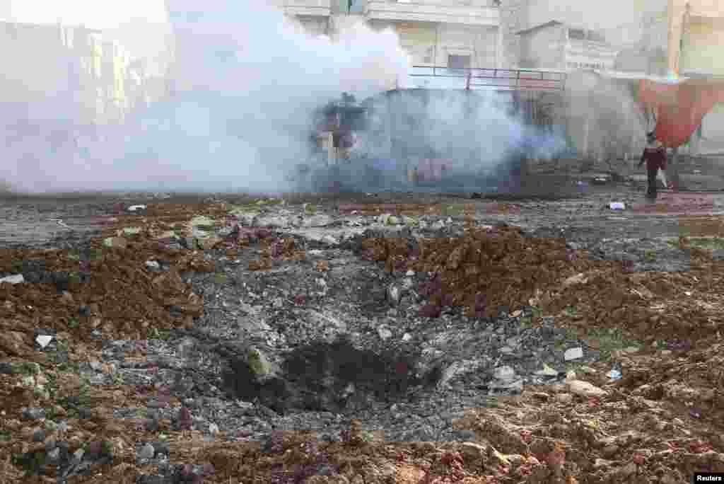 A man walks near a crater as smoke rises from a burning truck after what activists said were explosive barrels thrown by forces loyal to President Bashar al-Assad, al-Inzarat district, Aleppo, Feb. 18, 2014.