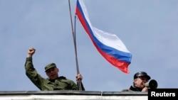 Pripadnik pro-ruskih snaga drži rusku zastavu u bazi ukrajinske mornarice u Sevastopolju