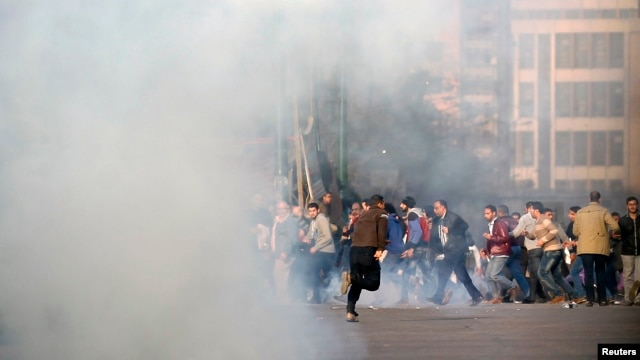 FILE - Anti-government protesters and members of the Muslim Brotherhood flee after teargas was fired by riot police during clashes in downtown Cairo, on the third anniversary of Egypt's uprising, Jan. 25, 2014.