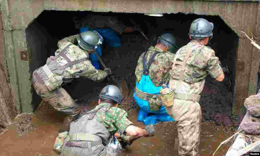 Các binh lính của lực lượng quốc phòng Nhật Bản tìm kiếm những người bị mất tích tại khu vực bị phá hủy do mưa lớn gây ra ở Aso, quận Kumamoto, ngày 16/7/2012
