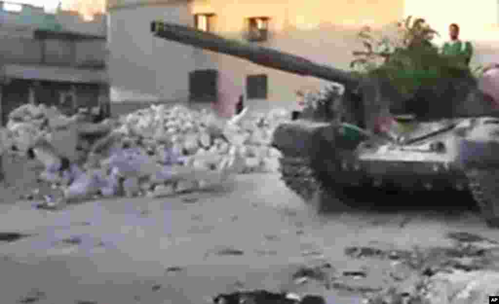 This image from amateur video released by the Ugarit News shows a Free Syrian Army solider driving a Syrian military tank in Aleppo, Syria, July 24, 2012.