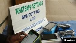 Un vendeur de rue ajuste les paramètres internet d'un client sur son téléphone à Harare, au Zimbabwe, le 13 janvier 2017.