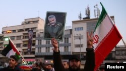 Un hombre iraní empuña un retrato del general Qassem Soleimani, mientras celebran el ataque con misiles iraníes a bases estadounidenses en Iraq, que no dejaron víctimas estadounidenses. Cortesía.