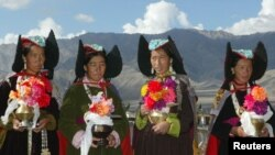 Ladakhi women, wearing 'perak', or traditional headgear, wait to welcome the Tibetan spiritual leader Dalai Lama outside a Buddhisttemple, August 23, 2002.