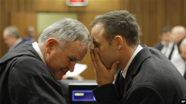 Oscar Pistorius talks with attorney Barry Roux, left, on the second day of trial, Pretoria, March 4, 2014.
