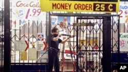 FILE - In this April 30, 1992 file photo, an L.A. police officer takes aim at someone attempting to steal something from a market in L.A. during the second night of rioting in the city in response to the acquittal of four police officers in the videotaped beating of Rodney King. (AP Photo/John Gaps III, File)