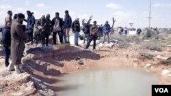 Fuerzas de oposición inspeccionan uno de los lugares donde cayó una de las bombas lanzadas por aviones de Gadhafi en Ras Lanouf.
