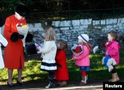 Britain's Queen Elizabeth receives flowers from children as she leaves a Christmas Day morning service at the church on the Sandringham Estate in Norfolk, eastern England, Dec. 25, 2013.