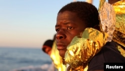 FILE - A migrant, covered with a thermal blanket, gazes at the sea aboard the former fishing trawler Golfo Azzurro of the Spanish NGO Proactiva Open Arms following a rescue operation near the coasts of Libya in the central Mediterranean Sea, Feb. 3, 2017.