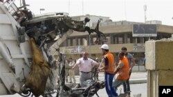 Petugas membersihkan puing-puing bekas ledakan bom mobil di Baghdad (19/4).